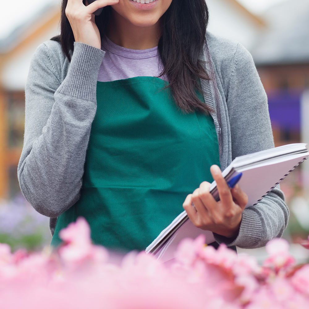 Garden center worker phoning while taking notes on flowers in center